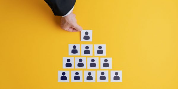 Top view of businessman hand making a pyramid shape of post it papers with people symbol on them un a conceptual image of business hierarchy.
